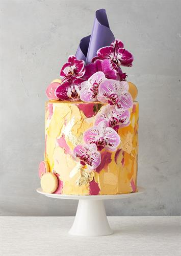 Dawn Food's Orchid Cake with golden yellow and magenta frosting, deep magenta and light pink orchids and a purple sugar shard on top.